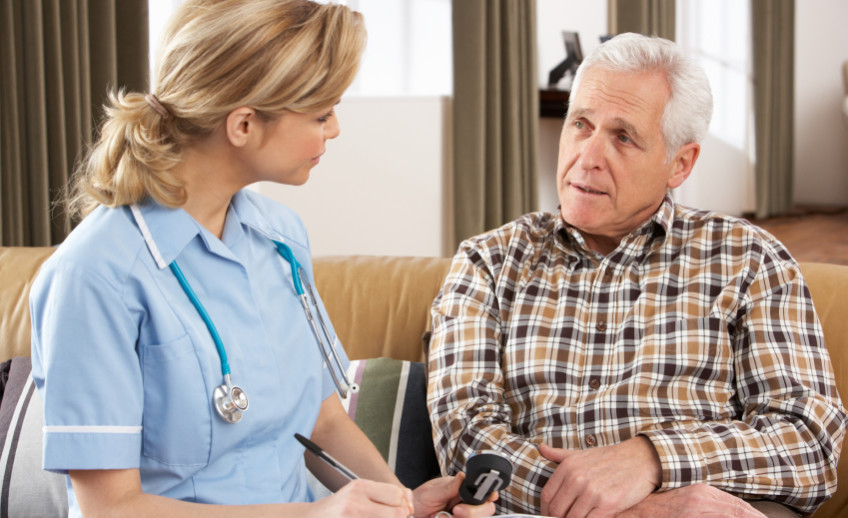Senior Man Talking To Health Visitor At Home